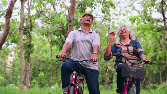 Senior couple riding bicycle in the park, Delhi, India