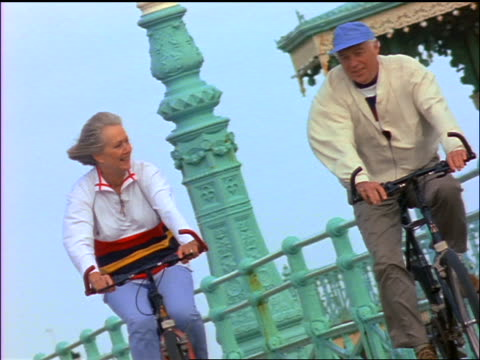 senior couple riding bicycles on boardwalk / brighton, england - giovane nell'animo video stock e b–roll