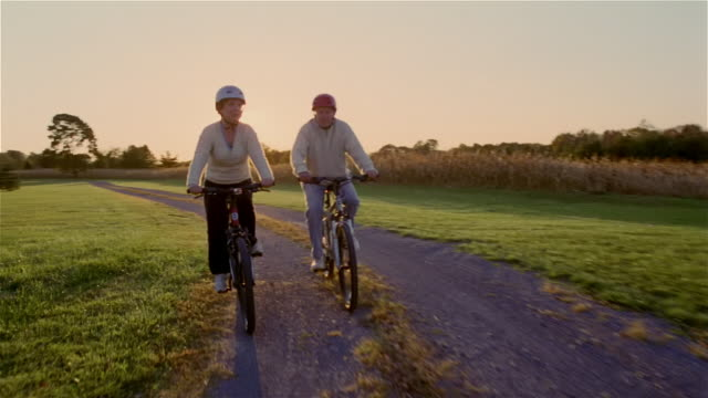 vídeos de stock, filmes e b-roll de senior couple riding bicycles on dirt road at sunset - active seniors