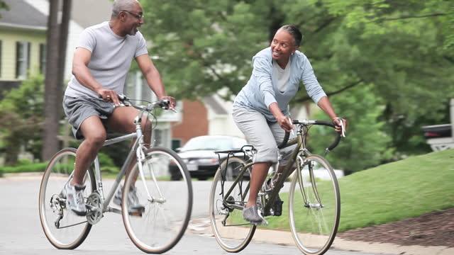 vídeos y material grabado en eventos de stock de senior couple riding bicycles on neighborhood street - suburbio zona residencial