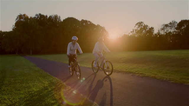 Senior couple riding bicycles on path at sunset