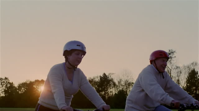 Senior couple riding bicycles through park at sunset