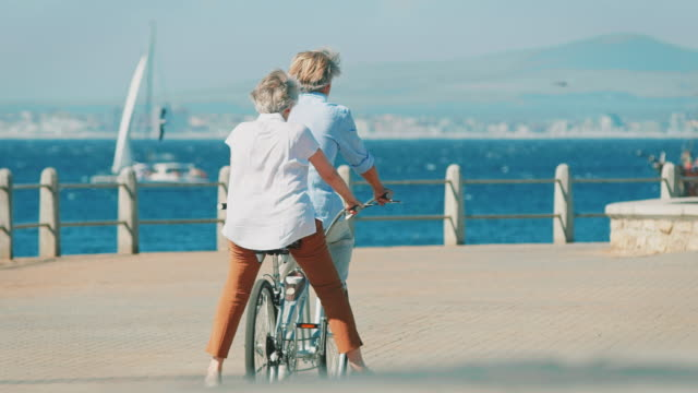 Senior couple riding tandem bike on promenade