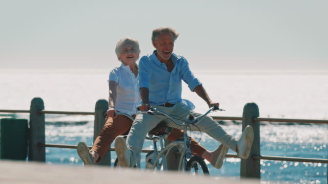 senior couple riding tandem bike on promenade - terza età video stock e b–roll