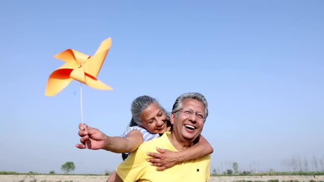 Senior couple rotating paper windmill, Haryana, India