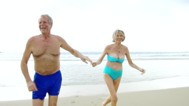 vídeos y material grabado en eventos de stock de senior pareja corriendo en la playa agarrados de la mano - traje de baño