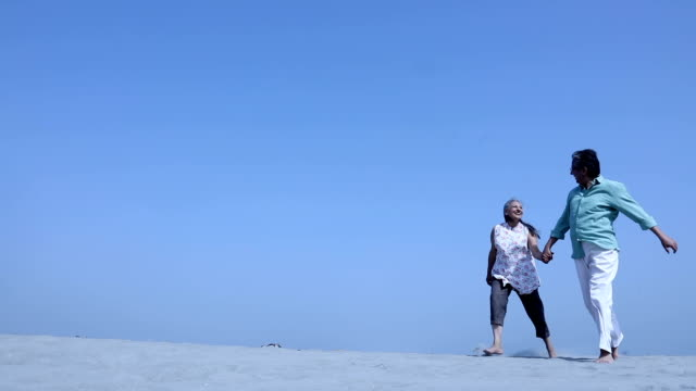 senior couple running on sand, haryana, india - open arms stock videos & royalty-free footage