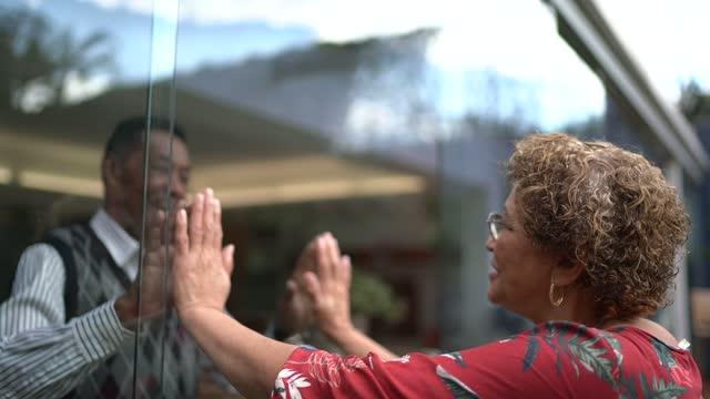 vídeos de stock e filmes b-roll de senior couple separated greeting through the window at home - sem saída conceito