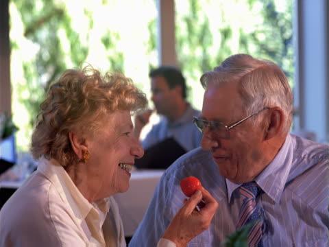 senior couple shares a strawberry - artbeats stock-videos und b-roll-filmmaterial