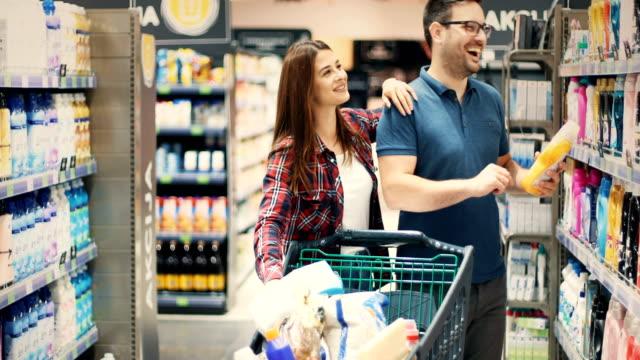 vidéos et rushes de magasinage de couples aîné dans le supermarché - lessive produit d'entretien
