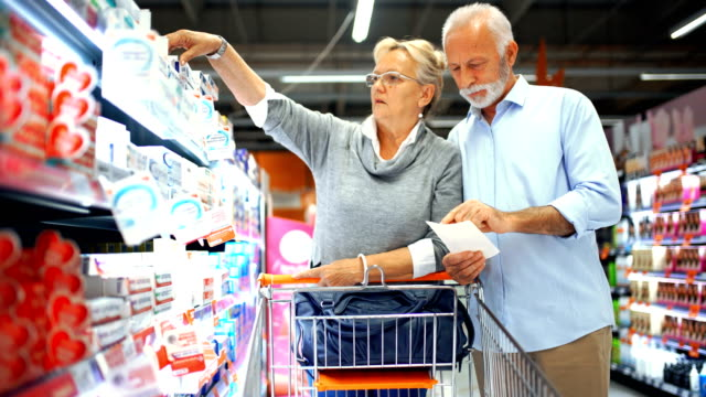senior couple shopping in supermarket. - retail stock videos and b-roll footage