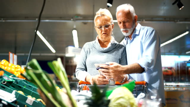 vídeos y material grabado en eventos de stock de pareja senior de compras en el supermercado. - incertidumbre