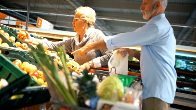 stockvideo's en b-roll-footage met senior paar winkelen in de supermarkt. - kiezen