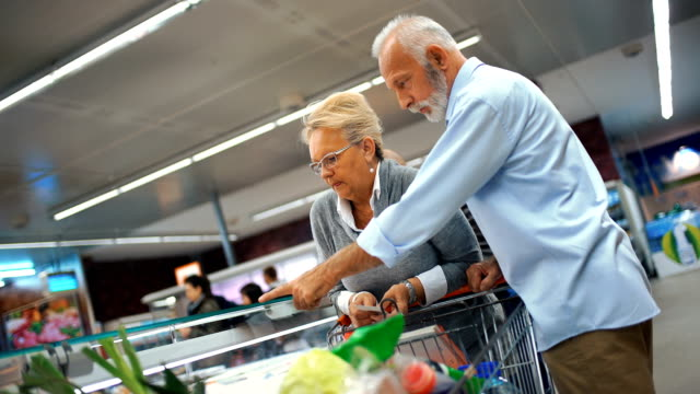 senior couple shopping in supermarket. - cibi surgelati video stock e b–roll