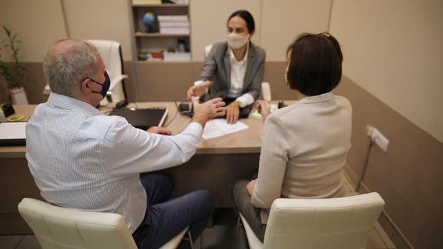 vídeos y material grabado en eventos de stock de pareja mayor firmando un contrato mientras tiene una reunión con agente de seguros en la oficina - contabilidad