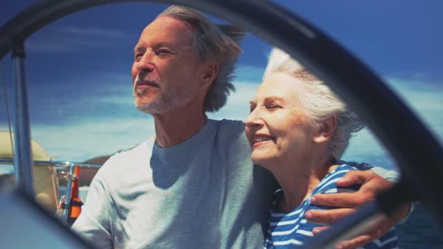 vídeos de stock, filmes e b-roll de canto do casal sênior enquanto desfruta em iate - riqueza