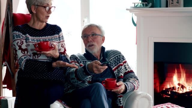 senior couple sipping tea by the fireplace and watching tv together - cosy stock videos & royalty-free footage