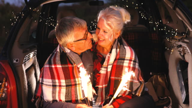 senior couple sit in open car trunk and hold spark sticks in their hands - boot stock videos & royalty-free footage