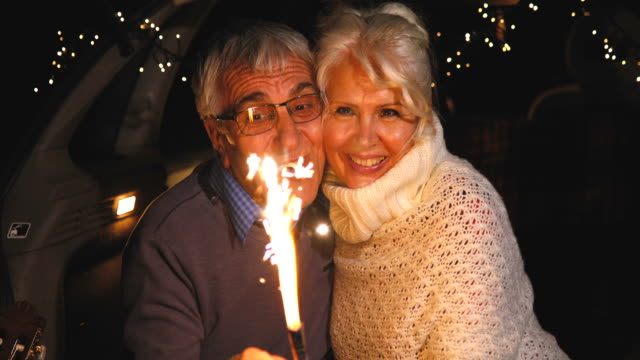 senior couple sit in open car trunk and hold spark sticks in their hands - sparkler stock videos & royalty-free footage