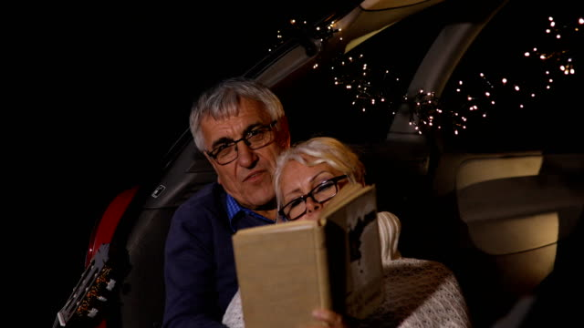 senior couple sit in open car trunk and reading a book - boot stock videos & royalty-free footage