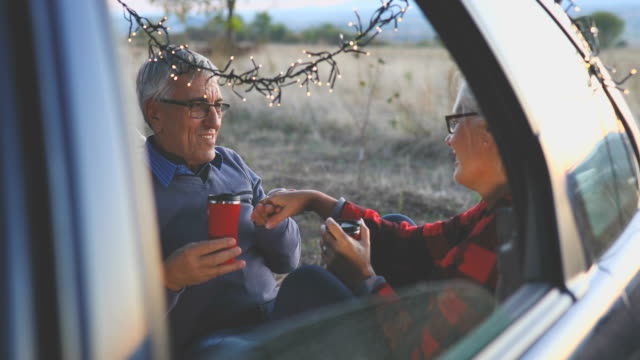 senior couple sit in open car trunk before a hike - senior couple stock videos and b-roll footage