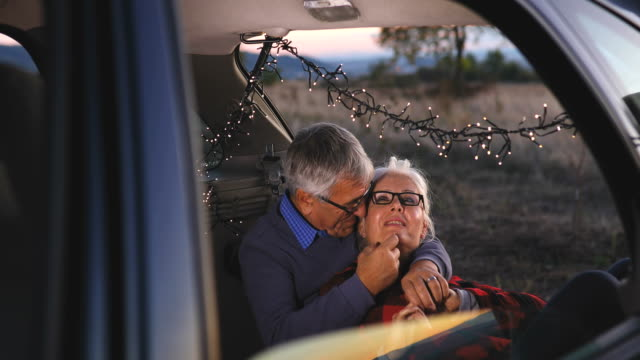 senior couple sit in open car trunk before a hike - blanket stock videos & royalty-free footage