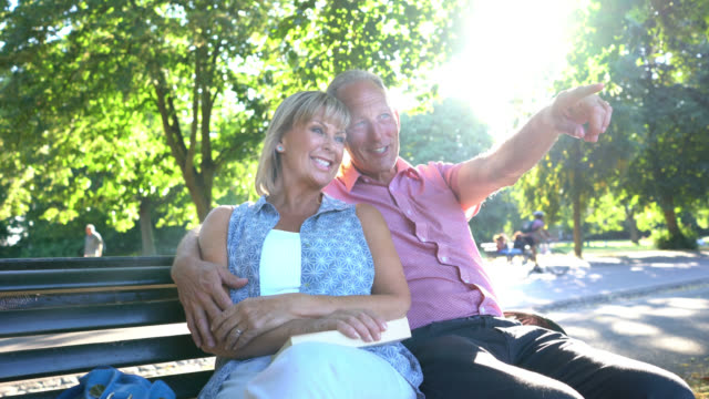 Senior couple sitting in a bench at the park talking and smiling