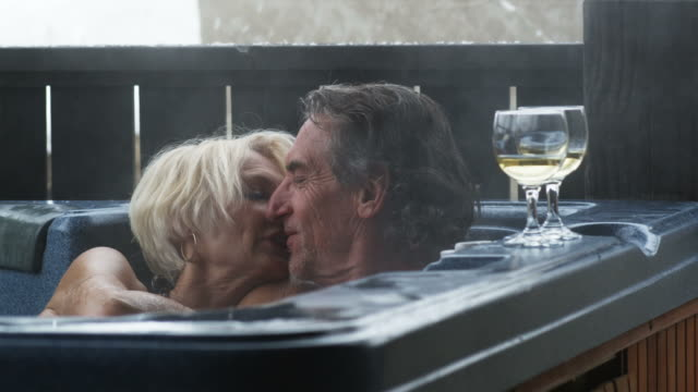 senior couple sitting in a hot tub kissing - hot tub stock videos & royalty-free footage