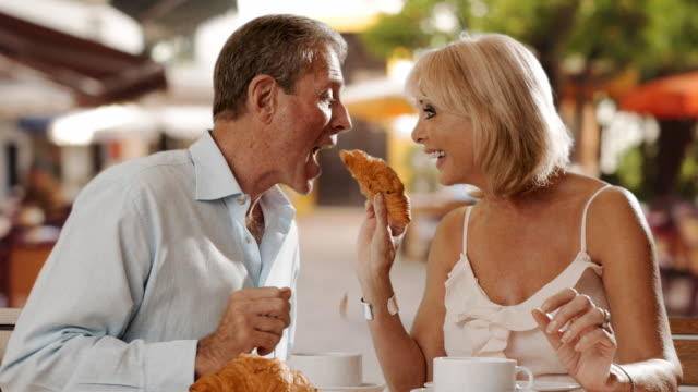 senior couple sitting in cafe eating croissant and laughing together. - croissant stock videos & royalty-free footage