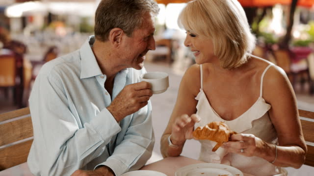 senior couple sitting in cafe eating croissant and laughing together. - heterosexual couple stock videos & royalty-free footage