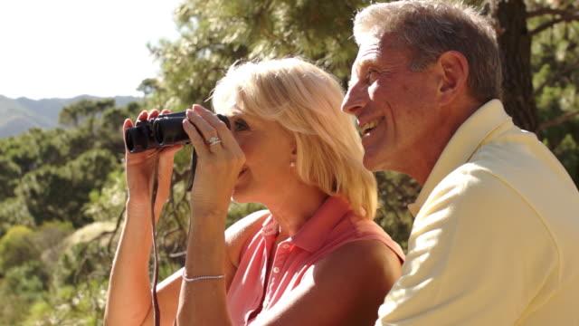 stockvideo's en b-roll-footage met senior couple sitting in countryside enjoying views with binoculars. - verrekijker