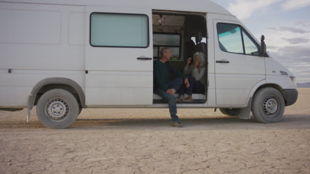 senior couple sitting in door of their campervan - baby boomer stock videos & royalty-free footage