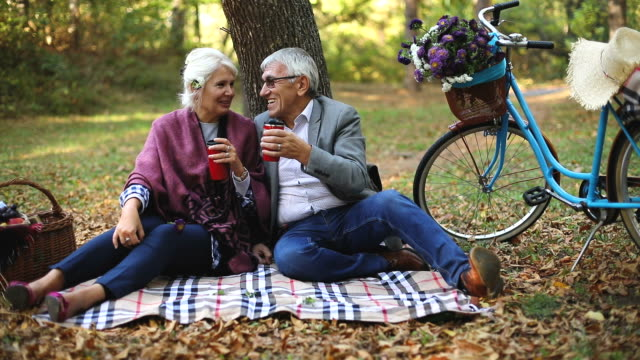Senior couple sitting in the forest while relaxing and drinking a cup of coffee