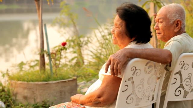 Senior couple sitting near river during sunset
