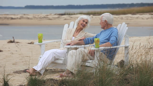 ws senior couple sitting on beach and talking, eastville, virginia, usa - eastville stock videos and b-roll footage