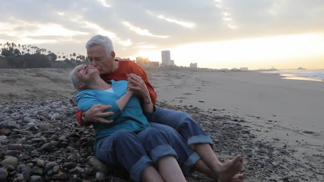 ws senior couple sitting on beach, man kissing woman / los angeles, california, usa - verlieben stock-videos und b-roll-filmmaterial