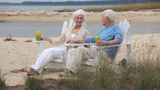 ws senior couple sitting on beach with drinks and talking, eastville, virginia, usa - eastville stock videos and b-roll footage