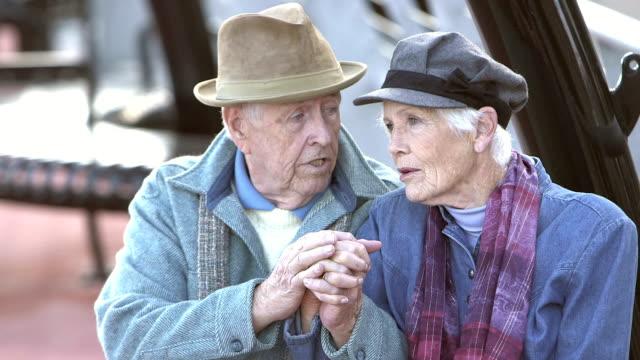 Älteres Paar auf Bank, die ernsthafte Diskussion