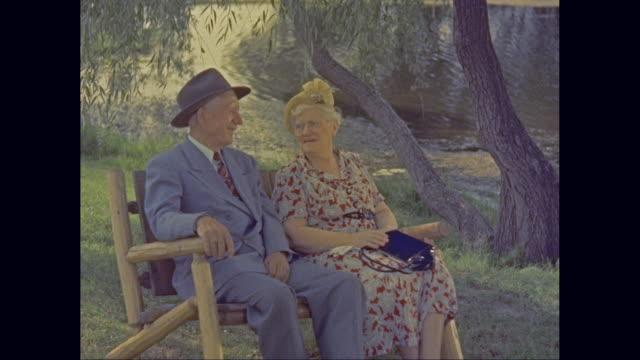 vidéos et rushes de ms senior couple sitting on bench in a park / united states - banc