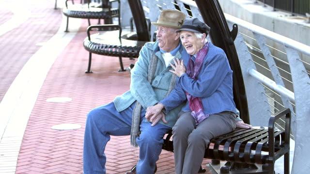 Senior couple sitting on bench, talking, enjoying view