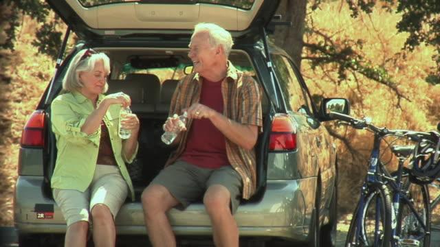 vidéos et rushes de ms senior couple sitting on car bumper drinking water / malibu creek, california, usa - eau potable