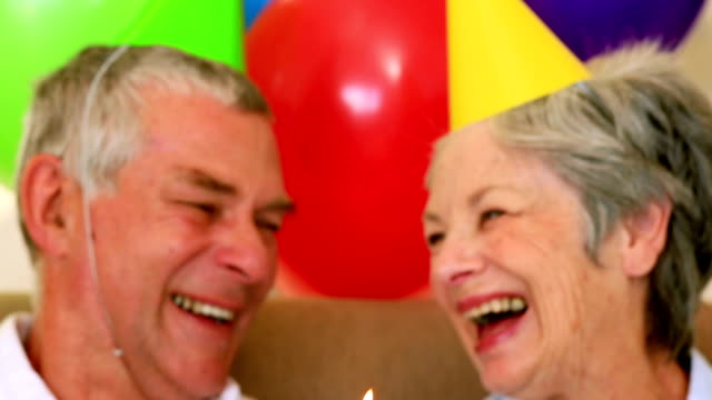 stockvideo's en b-roll-footage met senior couple sitting on couch celebrating a birthday - feestmuts