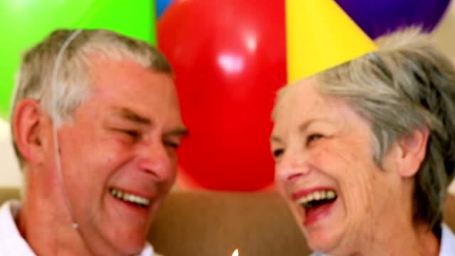 Casal Idoso sentado no sofá a celebrar um aniversário