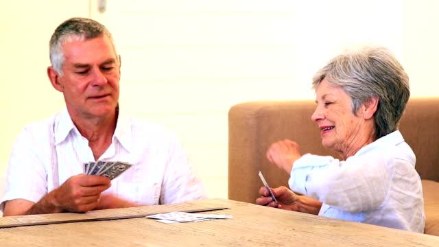 vídeos y material grabado en eventos de stock de pareja mayor sentado en el suelo naipes - mesa baja de salón