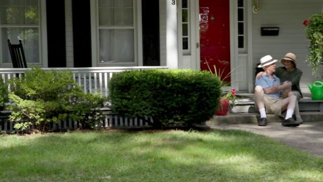 vídeos y material grabado en eventos de stock de senior couple sitting on front stoop - veranda