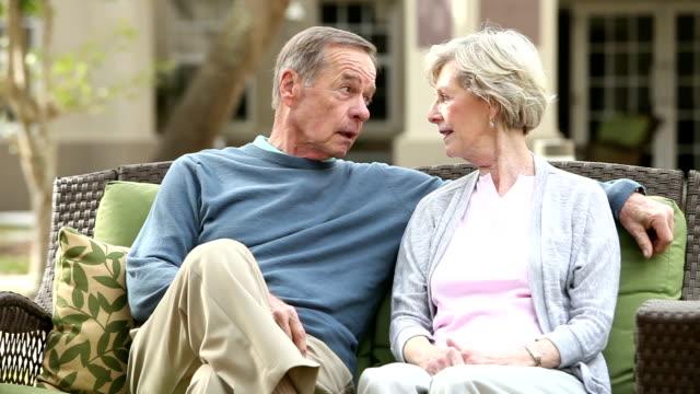 Älteres Paar auf Terrasse Sofa sitzen, reden, lachen