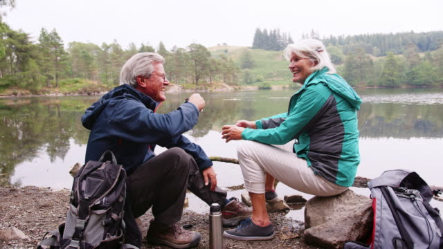 Senior couple sitting on rocks by a lake laughing and talking during a camping holiday, Lake District, UK