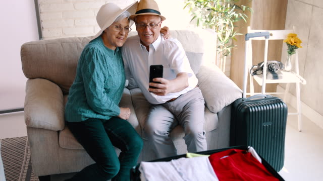 vídeos de stock e filmes b-roll de senior couple sitting on the sofa and taking a selfie - anticipation
