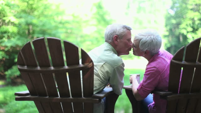 senior couple sitting outdoors in adirondack chairs - adirondack chair stock videos & royalty-free footage