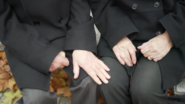a senior couple sitting together holding each others hands - mourning stock videos & royalty-free footage
